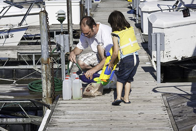girl and her father prepare for sailing fun