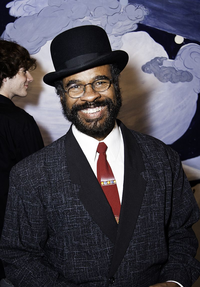 man in bowler hat smiles before colorful mural