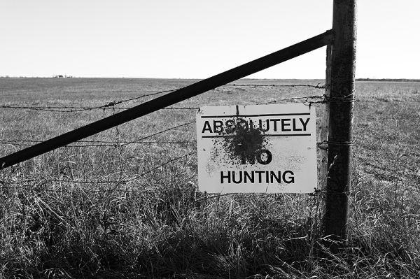 bullet riddled no hunting sign