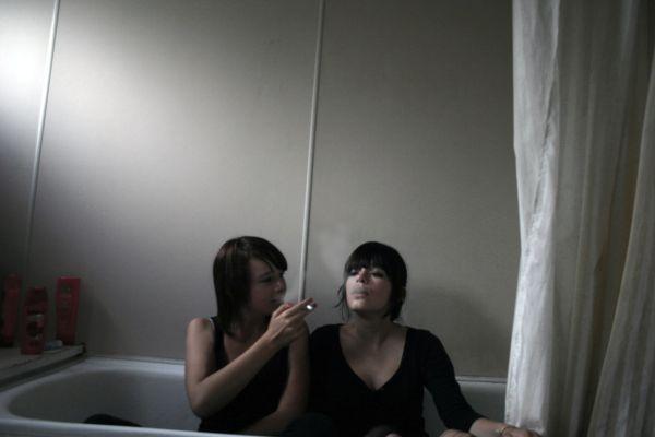 two girls smoking in a bathtub