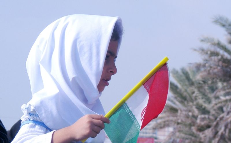a girl holding iran's flag
