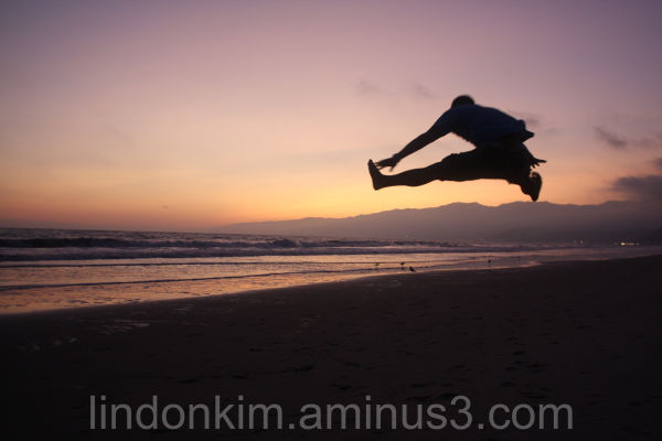 Action jumping photo taken on the beach at sunset