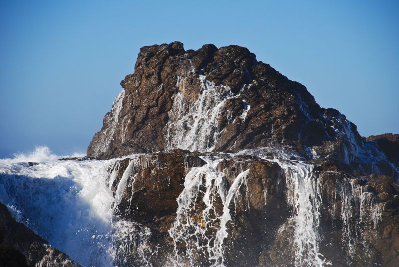waves crashing over massive rock