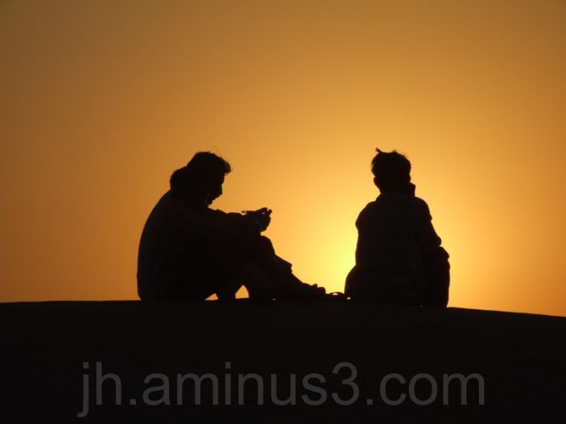 2 boys on dune top silouetted against sunset