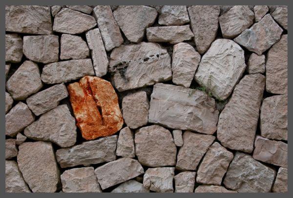 Orange rock in grey wall