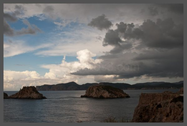 Dark clouds rolling in over islands in the sea