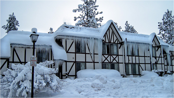 A snow laden apartment building with huge icicles.