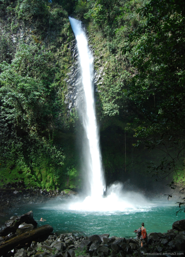 A large Costa Rican waterfall dwarfs a lone person