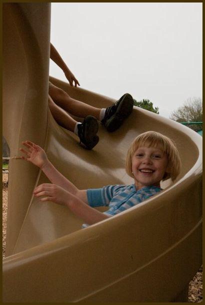 A little girl enjoying a slide at the park
