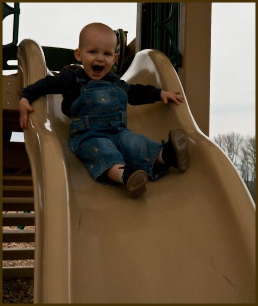 A baby boy experiencing a slide for the first time