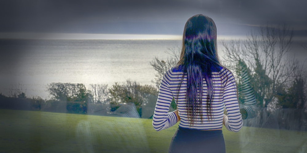 Girl looking out over the sea dreaming