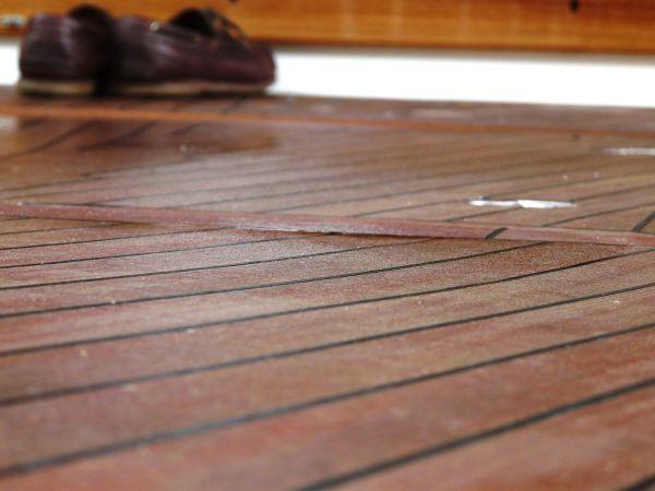 Zapatos nauticos sobre cubierta de teca de barco