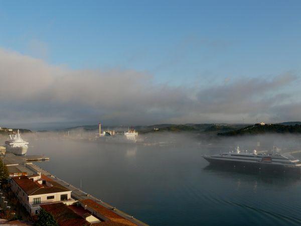 Barco entrando en el puerto de mahón con niebla