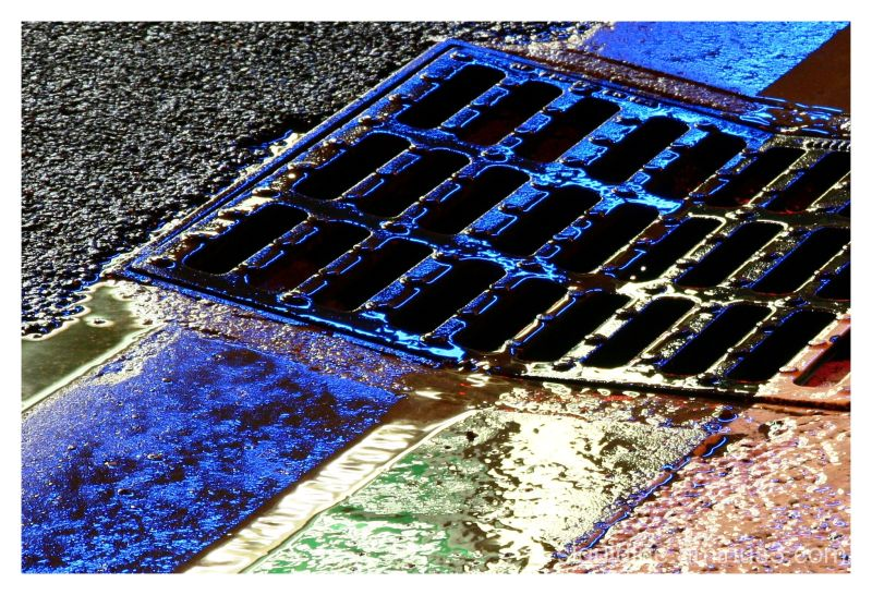 Neon lights reflecting on a manhole cover