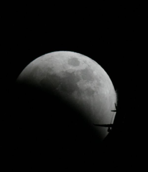 رد شدن هواپیما از کنار ماه در حال گرفت