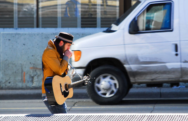 Downtown guitarist walking in the cold.