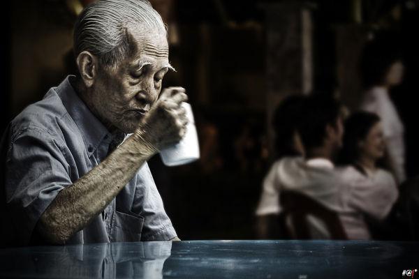 Elderly Asian man drinkin tea or coffee