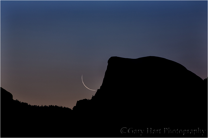 Thin crescent moon rises above Half Dome