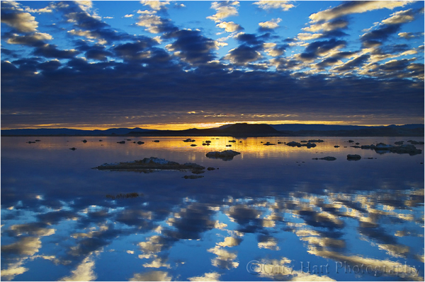 Rising sun and clouds reflected in Mono Lake