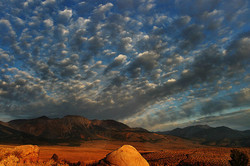 Granite boulder and marching clouds at sunrise