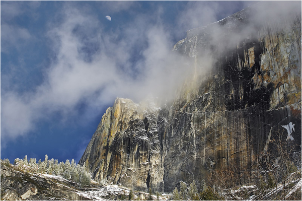 Winter moon and clouds above snowy Half Dome