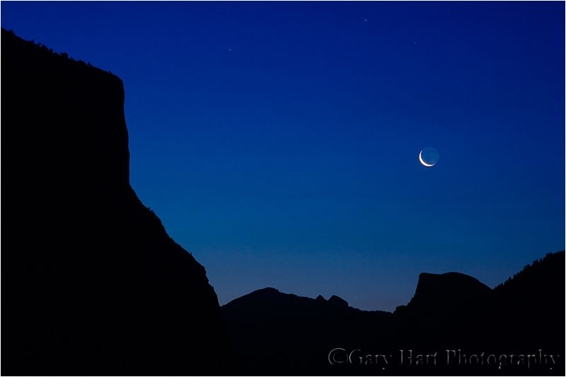 Crescent moon rises over Yosemite Valley at dawn
