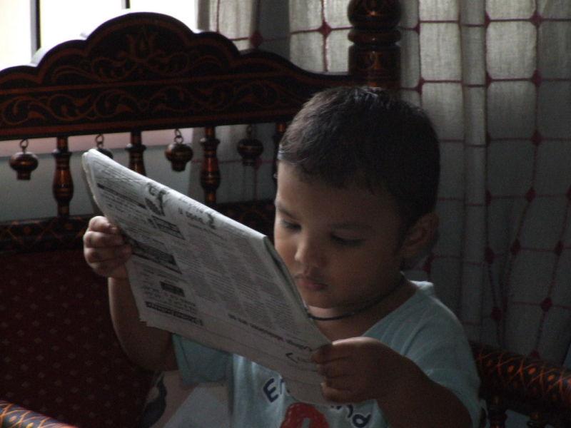 Kid engrossed in a newspaper