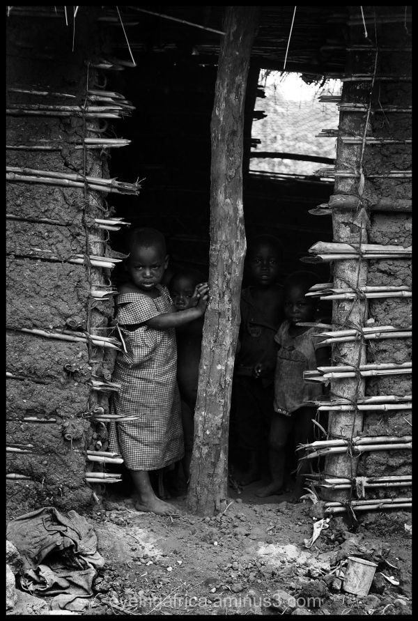 Children waiting at mud hut in Uganda