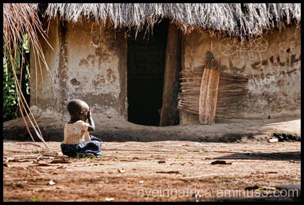 Little girl crying outside hut in Uganda