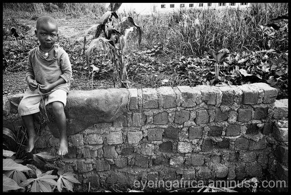 Ugandan boy sitting on the wall