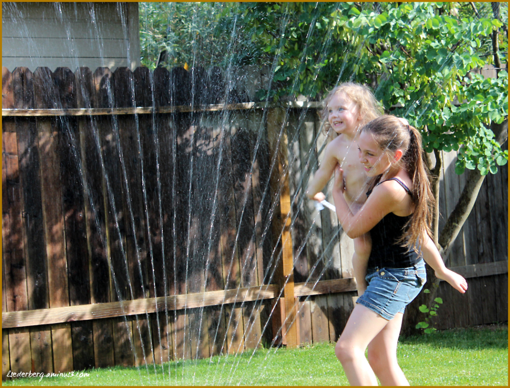 Grace and Madi play in sprinklers