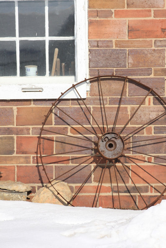 old wagon wheel against a brick barn