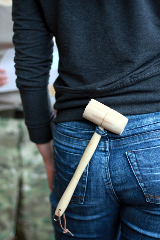 woman with a wood mallet tucked in a beltloop