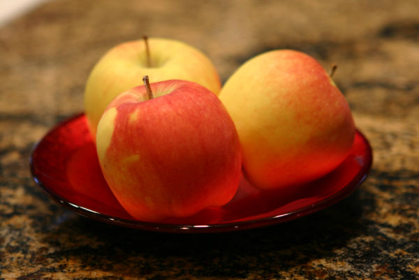 three apples on a red plate on granite