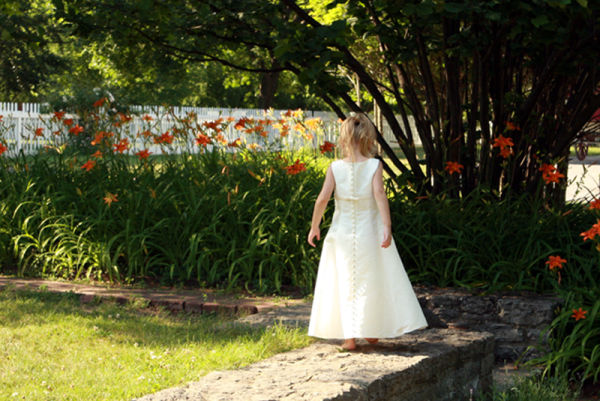 little girl walking away in a garden