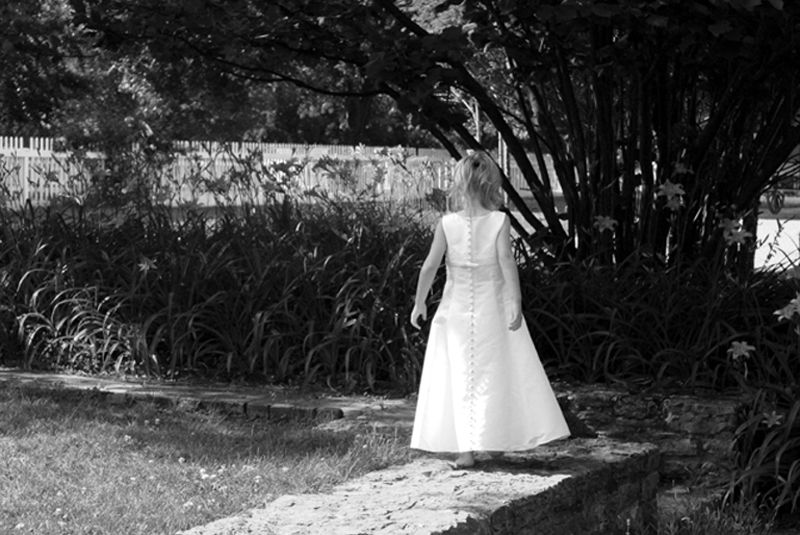 little girl walking in a garden bw