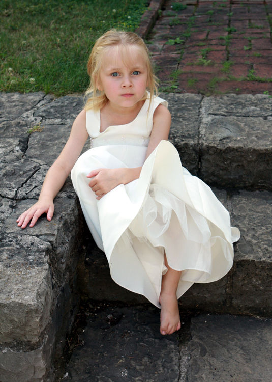 flower girl sitting on stone steps