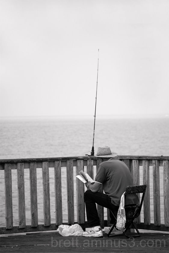 Lone fisherman reading on a pier