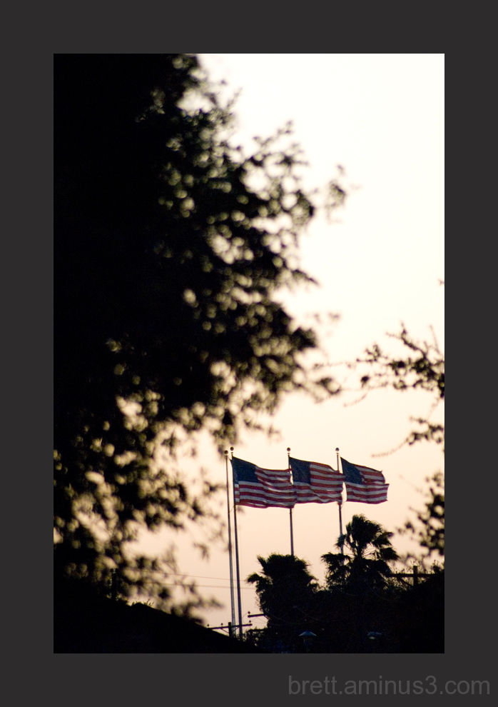 A silouhette picture of flags at sunset