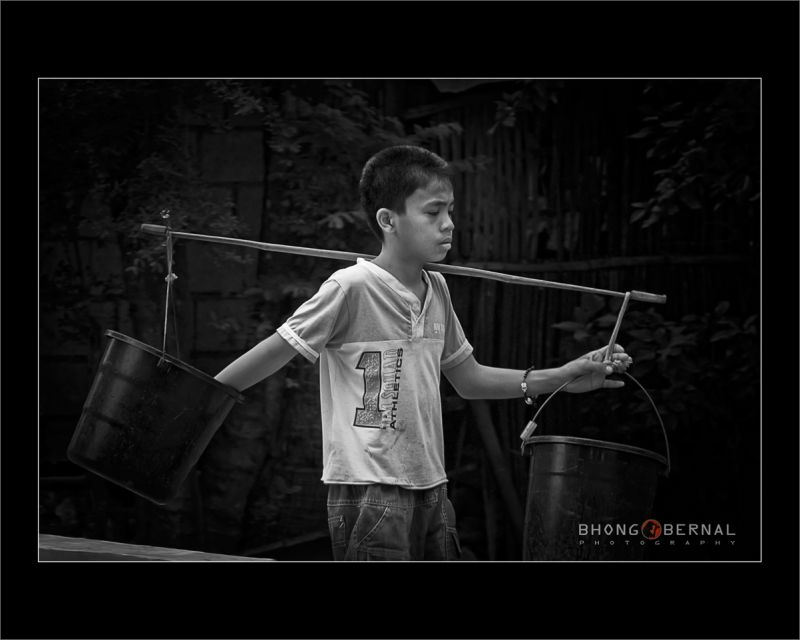 a Boy Petching Pails of Water