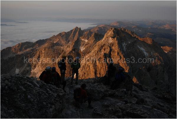 climbers watching the sunrise on the tetons