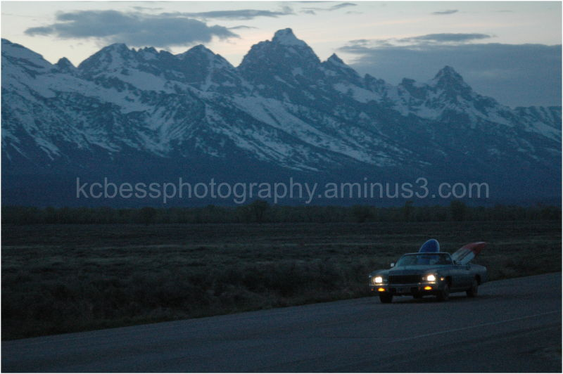 Kayaks in old car in front of Tetons