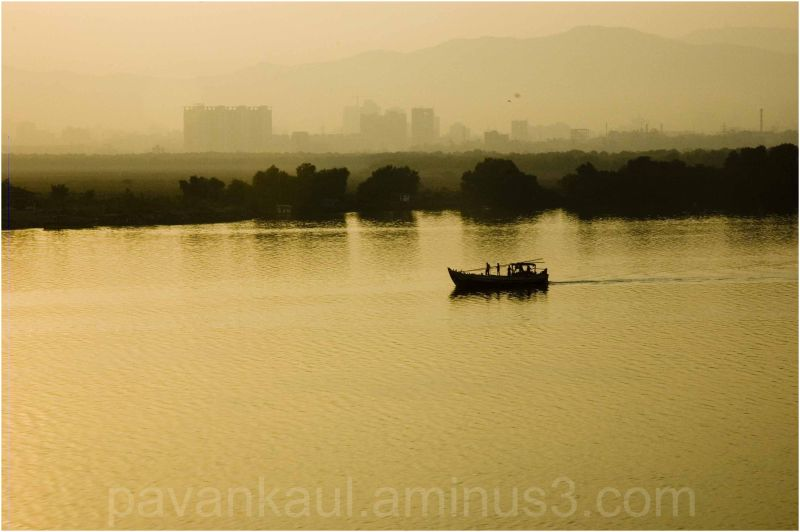Single boat on a creek against distant cityscape