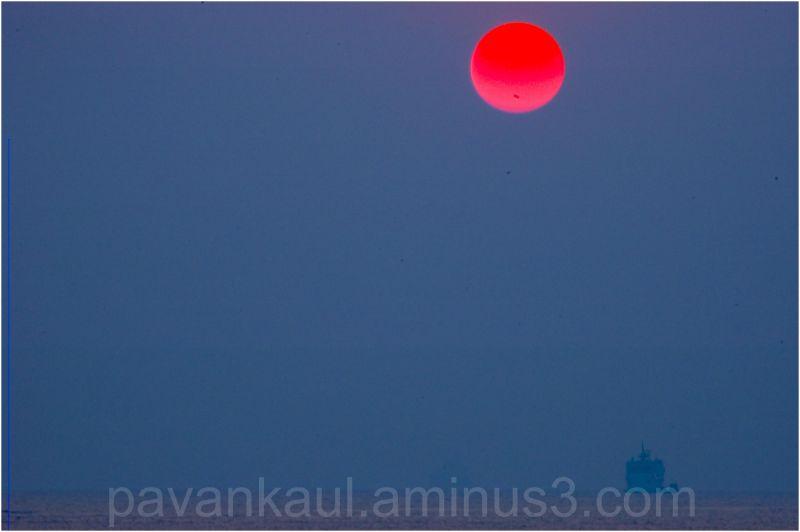 Sun setting over a lone ship on the horizon
