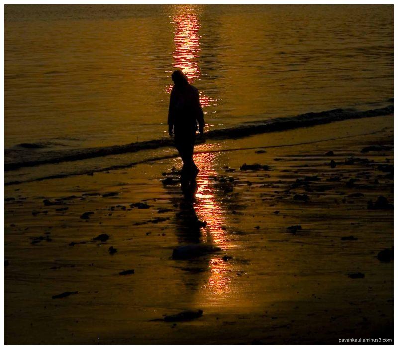 man walking on dirty beach