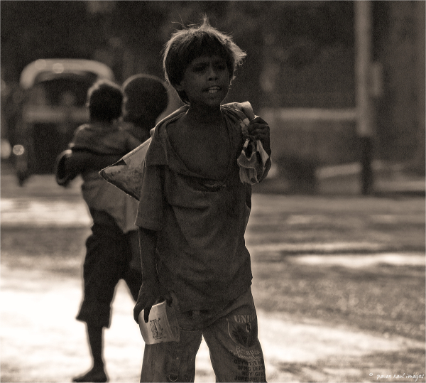 vagrant street child scrounging for scrap