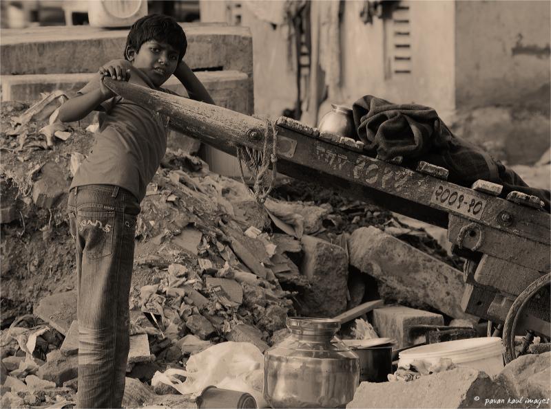 street child delivering scrap on handcart
