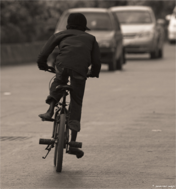 vagrant street child cycling against traffic
