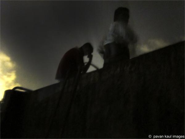 Men atop terrace water tank at night...?