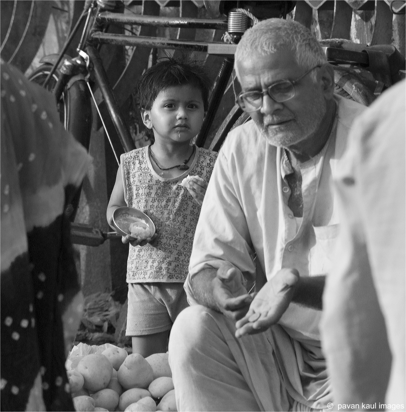 old man selling wares on streets with grandchild